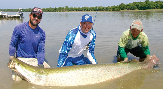AN APPROVED SPOT FOR LANDING A 300+ POUND ARAPAIMA. 9-WEIGHT OPTIONAL. THE FISH MEASURED 248 CENTIMETERS—JUST OVER EIGHT FEET. RAFAEL COSTA ON LEFT; JOHN SHERMAN IN THE MIDDLE; BOAT DRIVER BRAULINO ON RIGHT.