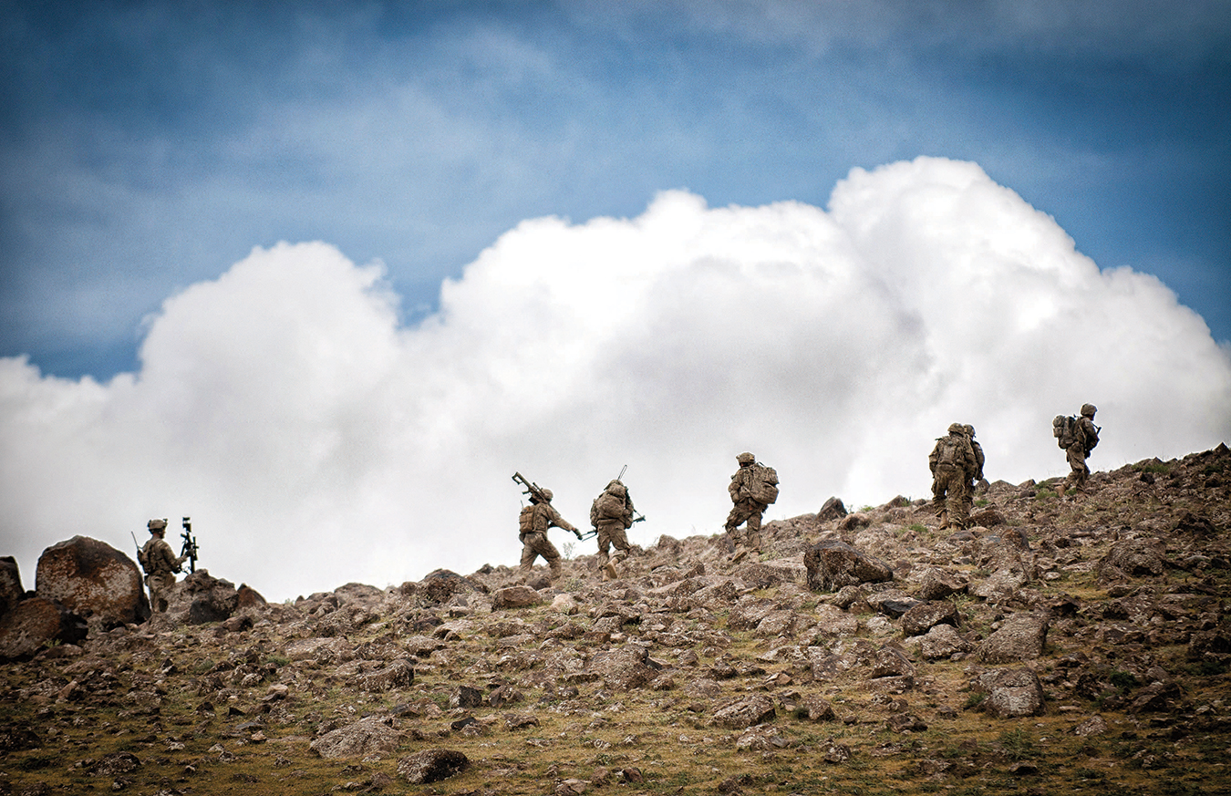 US ARMY SCOUT SNIPERS MOUNT A STRATEGIC HILL IN SOUTHEASTERN AFGHANISTAN TO PROVIDE OVERWATCH FOR AN INFANTRY PLATOON PREPARING TO CLEAR A TALIBAN CONTROLLED VILLAGE.