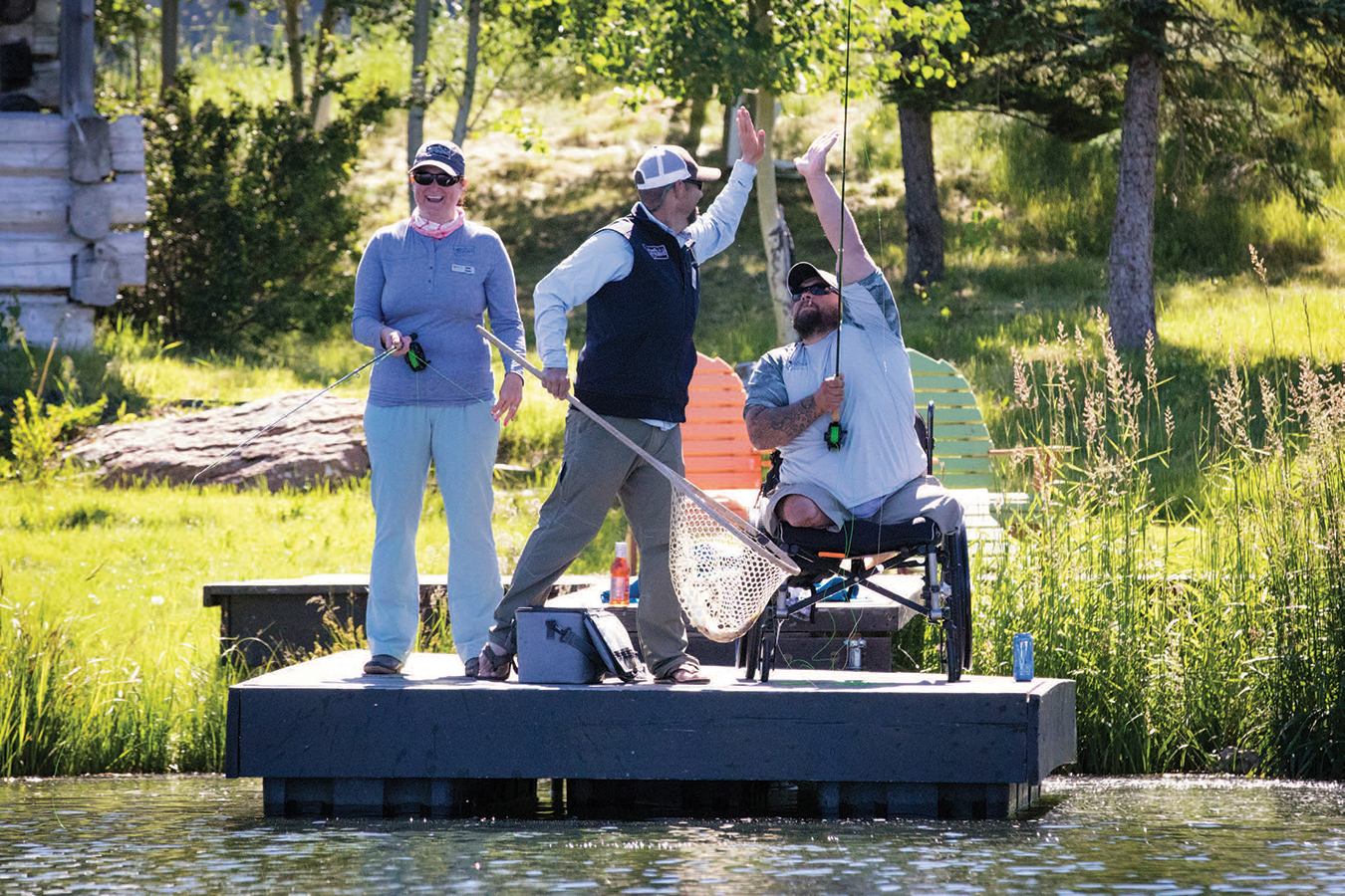 "PATRICK MYERS, A FORMER MARINE WHO WAS GRIEVOUSLY WOUNDED BY A ROADSIDE BOMB IN WESTERN IRAQ IN 2005, HIGHFIVES FLYFISHING GUIDE NATHAN GUFFEY AFTER LANDING A TROUT. A PARTICIPANT OF AN EARLIER ""SOLO FX,"" PATRICK RETURNED TO WQW IN 2017 TO SHARE HIS NEW LOVE OF FLYFISHING WITH WIFE, MINDY, IN A ""COUPLE'S FX."""